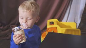 Boy eating ice cream sitting in a high chair. cute child enjoying an ice cream in a waffle cone. looks toward. Boy eating ice cream sitting in a high chair stock footage