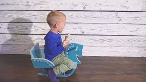 Boy eating ice cream sitting in a high chair. cute child enjoying an ice cream in a waffle cone. looks toward. stock video