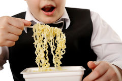 Boy eating instant noodles Stock Photography
