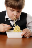 Boy eating instant noodles Royalty Free Stock Images