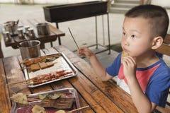 Boy eating kebab Stock Image