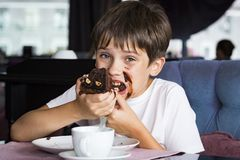 The boy is eating a large piece of cake stock photos