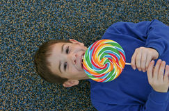 Boy Eating Lollipop. A Boy Laying Down Eating a Lollipop Royalty Free Stock Images