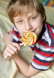 Boy eating lollipop. Boy eating bright lollipop at home Royalty Free Stock Photography