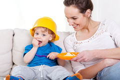 Boy eating meal and his mum Stock Images
