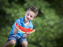 Boy eating melon. Happy boy sitting outside eating a water melon slice Stock Images