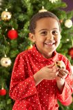 Boy Eating Mince Pie In Front Of Christmas Tree Stock Images