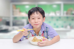 Boy eating noodle by chob stick Stock Photo