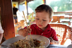 Boy eating noodles Stock Photos