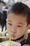 Boy eating noodles Royalty Free Stock Image