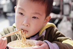 Boy eating noodles Stock Image