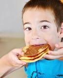 Boy eating pancakes Stock Image
