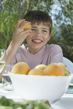 Boy Eating Peach At Garden Table Stock Images