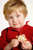 Boy eating a  peanut butter and jelly sandwich. A young boy holding a peanut butter and jelly sandwich (focus is on the face Stock Photos