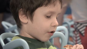 Boy eating pizza stock footage