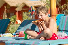 Boy eating pizza outdoors Royalty Free Stock Images
