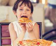 Boy eating pizza in Royalty Free Stock Images
