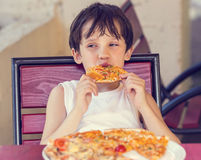 Boy eating pizza Stock Images