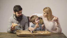 Boy eating pizza on a wooden background. Tasty pizza. Concept of nutrition. Portrait of happy family eating pizza. Happy stock footage
