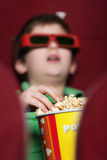 A boy eating popcorn Stock Photography