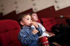 Boy eating popcorn Stock Images