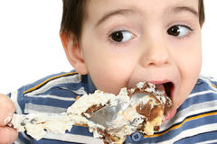 Boy Eating Possum Pie. Close up of a two year old boy eating possum pie with a big silver spoon. Shot in studio over white Royalty Free Stock Images