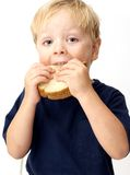 Boy eating sandwich. Boy taking a big bite of its peanut butter sandwich Stock Image