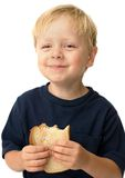 Boy eating sandwich. Little boy showing satisfaction while eating a peanut butter sandwich Royalty Free Stock Photo