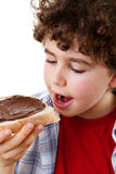 Boy eating sandwich with chococolate cream Stock Images