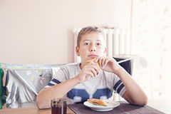 Boy eating sandwich. Young boy seating and eating sandwich Stock Photography