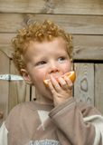 Boy eating Sour Fruit. Boy (3) taking a big bite out of a grapefruit Royalty Free Stock Image