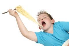 Boy Eating Spaghetti. Boy eating big fork full of spaghetti. Shot in studio on white background Royalty Free Stock Images