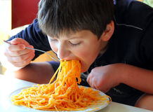 Boy eating spaghetti Stock Image