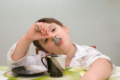 Boy eating with spoon Stock Images