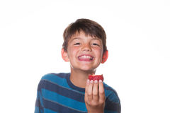 Boy eating strawberry. Younger boy eating a strawberry and smiling at the camera stock photos