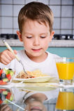 Boy eating at the table, looking at the plate. vertical Stock Photography