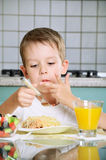 Boy eating at the table vertical Royalty Free Stock Images