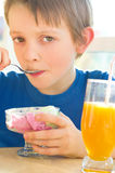 Boy eating a tasty ice cream. Cute boy eating a tasty ice cream and drinking an orange juice Stock Photography