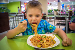 Boy eating thai yellow noodle and fried vegetables Royalty Free Stock Images