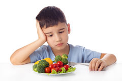 Boy eating vegetables. Sad boy doesn't want eat healthy vegetables Stock Image