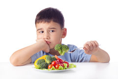 Boy eating vegetables. Sad boy doesn't want eat healthy vegetables Royalty Free Stock Images