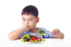 Boy eating vegetables Royalty Free Stock Images