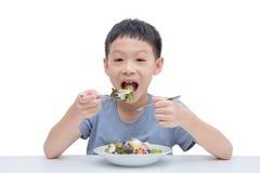 Boy eating vegetables salad Stock Photos