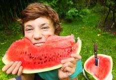 Boy eating water melon grimacing Royalty Free Stock Image