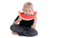 Boy eating a watermelon on the floor Royalty Free Stock Image