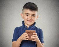 Boy eating whole bar of chocolate Royalty Free Stock Photo