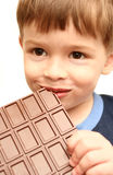 The boy eats. A greater chocolate Stock Images