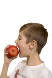 The boy eats an apple Stock Photography