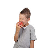 Boy eats apple. Joyful teenage boy aggressive bites off a big red apple in hand isolated on white background is square Stock Photography