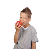 Boy eats apple. Joyful teenage boy eats big red apple in his hand isolated on white background is square Stock Image